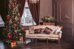 Luxurious sofa in the interior. New Year celebration. Christmas tree decorated with toys and a garland. Luxurious sofa in the interior. New Year celebration Royalty Free Stock Image