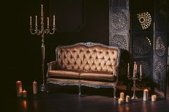 A luxurious sofa made of golden fabric in a modern interior decorated with decor and candles. In dark colors. Luxurious sofa in a modern interior, decorated Royalty Free Stock Photo