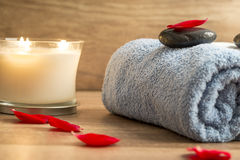 Luxurious spa setting with a rolled blue towel, romantic candle Royalty Free Stock Photo