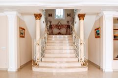 Luxurious staircase with marble steps and decorative and  orname. Ntal iron railings. On the top are decorating furniture in neoclassical style, a table with Stock Photo