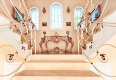 Luxurious staircase with marble steps and decorative and  orname. Ntal iron railings. On the top are decorating furniture in neoclassical style, a table with Royalty Free Stock Photos