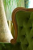 Luxurious stuffed chair. Close shot of part of a green luxurious antique armchair stock image