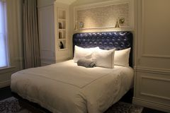 Luxurious suite with king sized bed and deep blue headboard, The Adelphi Hotel, Saratoga Springs, New York, 2018. Inviting scene with king sized bed and deep Royalty Free Stock Images