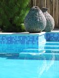 Luxurious swimming pool. Clear blue water in luxurious tropical swimming pool, two wicker baskets at side of steps Royalty Free Stock Photography