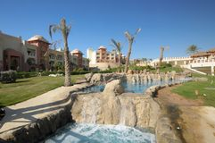 Luxurious swimming pool. Waterfall in luxurious swimming pool, resort complex buildings in background Stock Images
