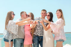 Luxurious vacation concept. A group of happy friends on a blue sea background. Adults partying in sun glasses and summer royalty free stock photos