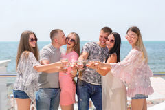 Luxurious vacation concept. A group of happy friends on a blue sea background. Adults partying in sun glasses and summer stock images