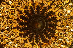 Luxurious vintage chandelier bottom view. Beautiful vintage golden illuminated chandelier bottom view Stock Photo