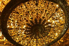 Luxurious vintage chandelier bottom view. Beautiful vintage golden illuminated chandelier bottom view Royalty Free Stock Photography
