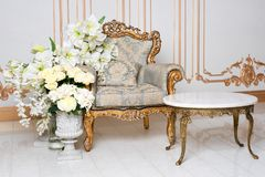 Luxurious vintage interior in the aristocratic style with elegant armchair and flowers. Retro, classics. Luxurious vintage interior in the aristocratic style Stock Images