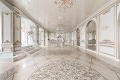 Luxurious vintage interior with fireplace in the aristocratic style. Large Windows and mirrors. Columns and arches. Ornament on the glossy floor Royalty Free Stock Photos