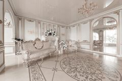 Luxurious vintage interior with fireplace in the aristocratic style. Large Windows and mirrors. Columns and arches. Ornament on the glossy floor Royalty Free Stock Photo