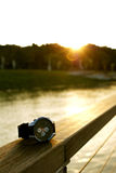 Luxurious Watch. A luxurious watch siting on the railing of a boardwalk at a lake duirng a wonderful sunset royalty free stock images