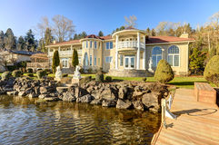Luxurious waterfront home backyard view. Luxurious Mediterranean style waterfront home exterior with view of the backyard area and private dock in Lake stock photo