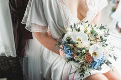 Luxurious wedding bouquet made of roses, carnation and hydrangea. In a hands of beautiful bride in lingerie Royalty Free Stock Photography