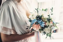 Luxurious wedding bouquet made of roses, carnation and hydrangea. In a hands of beautiful bride in lingerie Stock Images