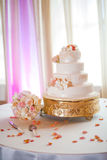 Luxurious wedding cake. And bouquet on table with flower petals scattered in foreground Stock Images
