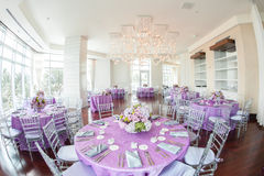 Luxurious wedding reception. With flower bouquets on lilac covered tables Stock Photography