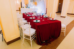 Luxurious wedding table with red tablecloth.  Wedding celebration Royalty Free Stock Photos