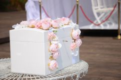 Casket for a wedding for gifts. Luxurious white wooden box decorated with pink flowers. Casket for a wedding for gifts stock photos