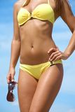 Luxurious woman in bikini with sunglasses. Torso of luxurious woman in bikini with sunglasses stock photography