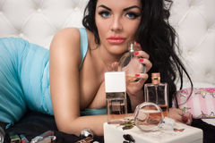 Luxurious woman with perfume. Luxurious woman in blue dress holds a bottle of perfume stock photos