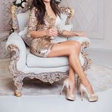 A luxurious woman sits in an expensive chair against the backdro royalty free stock photography