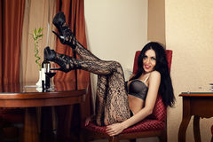 Luxurious woman sitting in a chair in lingerie Royalty Free Stock Image
