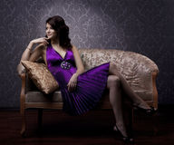 Luxurious woman sitting on a gold vintage couch Royalty Free Stock Photography