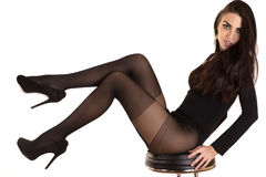 Luxurious woman in stockings sitting on a chair Stock Photography