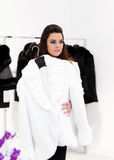 Luxurious woman tries on a fur coat. Luxurious woman tries on a white mink fur coat royalty free stock photography