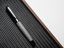 Luxurious writing tools. Luxurious rollerball pen on a carbon surface Stock Image
