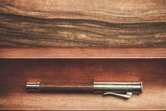 Luxurious writing tools. Luxurious rollerball pen on a wooden background Royalty Free Stock Photos