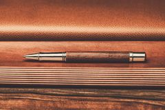 Luxurious writing tools. Luxurious rollerball pen on a wooden background Royalty Free Stock Photography