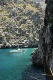 Luxurious yacht on coast. Scenic view of luxurious motor yacht by rocky Majorcan coastline, Balearic Islands, Spain Royalty Free Stock Photo