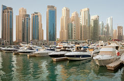 Luxurious Yachts and Boats in Front of Dubai Marina Skyscrapers Stock Photo