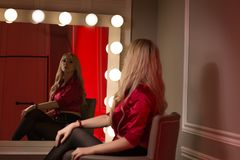 Luxurious blonde model wears red silk blouse, looking on her ref. Luxurious young woman wears red silk blouse, looking on her reflection in the big mirror with Royalty Free Stock Images