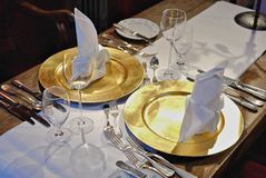 Luxuriously laid dining table. Two place settings on luxuriously laid table with gold plates Royalty Free Stock Images