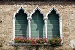 Luxuriöser blumiger Balkon in der venetianischen Art mit gewölbten Fenstern Stockfotografie