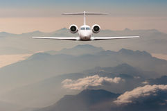 Luxury Airplane fly over clouds and Alps mountain on sunset. Front view of a big passenger or cargo aircraft, business Royalty Free Stock Photos