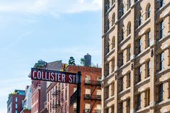 Luxury apartment buildings in Tribeca in New York. Low angle view of Collister Street name sign against luxury apartment buildings in Tribeca North District of royalty free stock photography