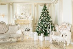 Luxury apartment decorated for christmas. Xmas tree with presents underneath in living room royalty free stock images