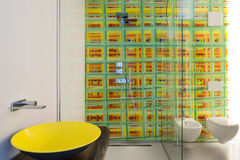 Luxury apartment, modern bathroom. With yellow sink, shower and colored tiles stock photography