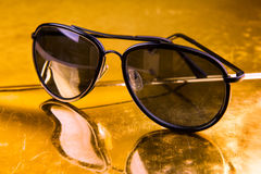 Luxury aviator sunglasses on golden background Stock Images