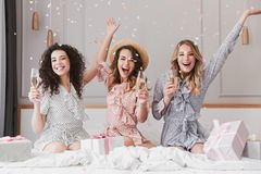 Luxury bachelorette party in posh apartment while happy young th. Ree women 20s having fun and drinking champagne under falling confetti stock photos