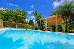 Luxury backyard swimming pool. A luxury backyard swimming pool and bar-b-que area is surrounded by beautiful lawns and gardens, and many large tropical palm royalty free stock photo