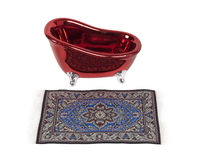 Luxury Bath. Shown by an intricate rug in front of a red antique claw footed bathtub - Path included Royalty Free Stock Image