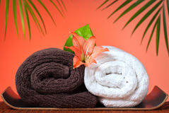 Luxury bath towels background. Spa & massage still life: Luxury bath towels and flowers royalty free stock photography