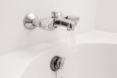 Luxury bath tub and faucet with water. Royalty Free Stock Photo