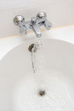 A Luxury bath tub and faucet with water. Royalty Free Stock Photo